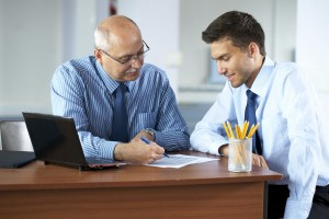 two businessman discuss something, office background